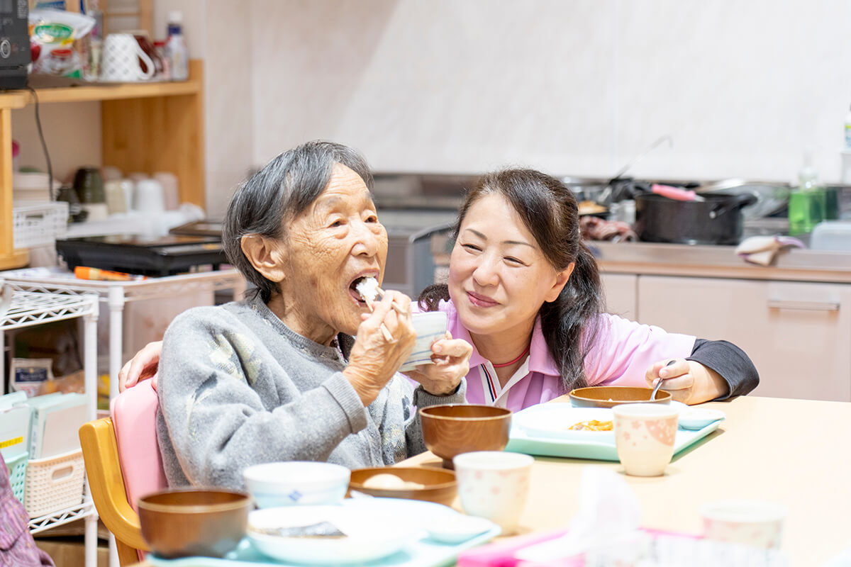 食事の様子を見守る女性