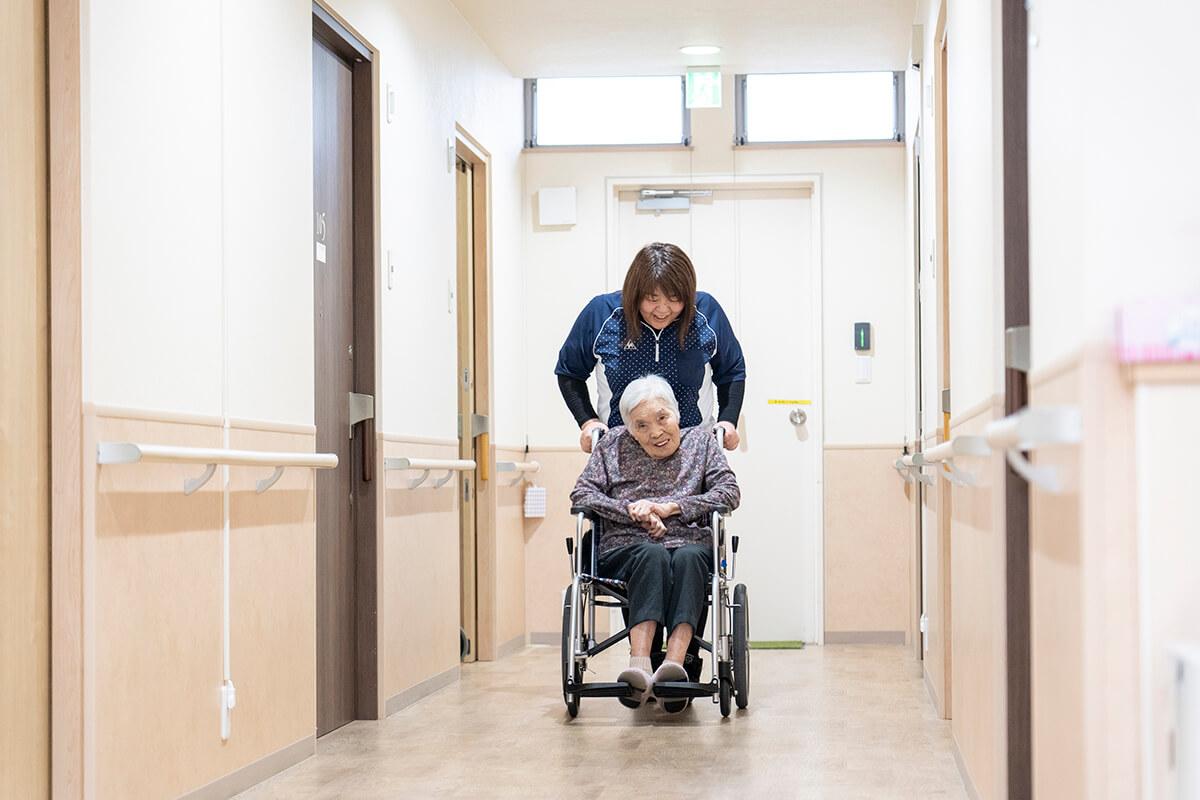 老人の乗った車椅子を押すスタッフ