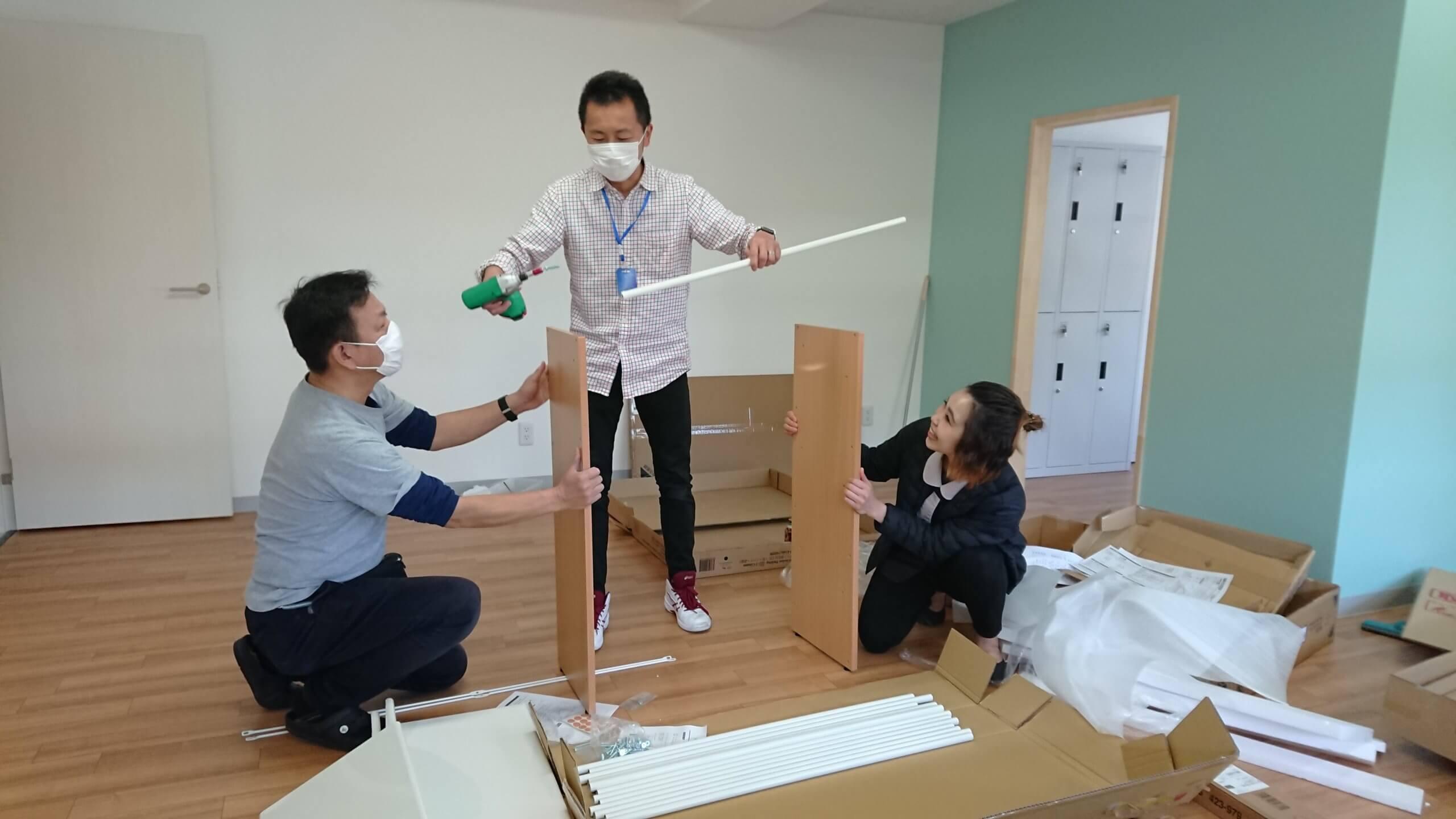 協力して家具を組み立てる男女スタッフ