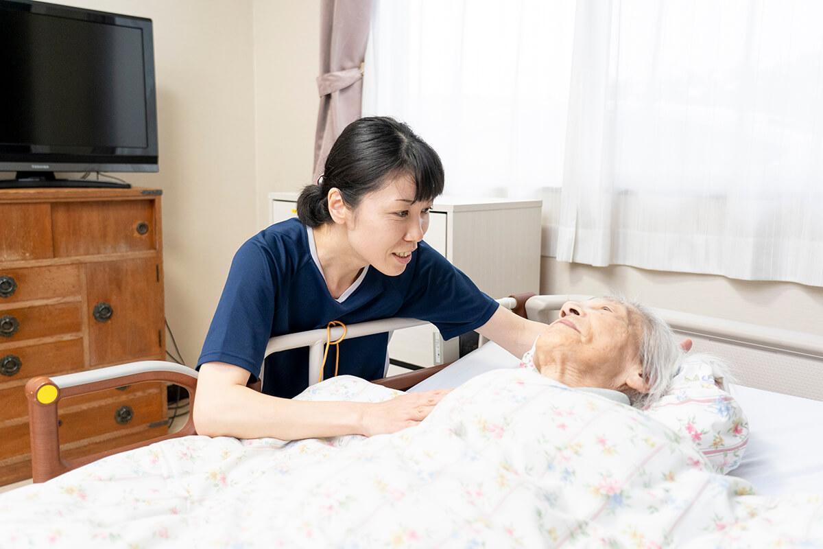 寝ている老人に声をかけるスタッフ