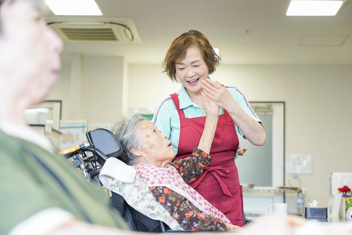 老人の手を取りサポートをする女性スタッフ